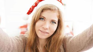Christmas portrait of beautiful girl. Teenager wearing santa claus hat photo