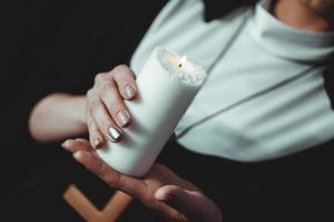 Young catholic nun is holding candle in her hands photo