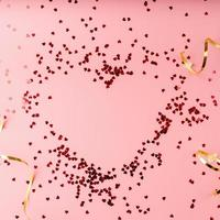 Red heart shape confetti heart top view flat lay on pink background photo