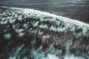 Aerial view to ocean waves. Blue water background photo