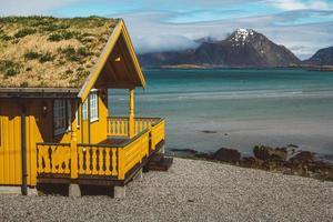 Casa de madera amarilla con musgo en el fondo del mar y las montañas foto