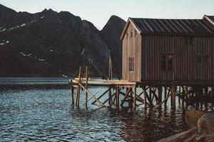 Antiguas casas de pesca de madera cerca del lago con el telón de fondo de las montañas foto