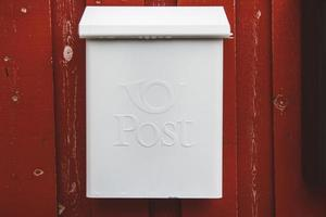 A white mailbox on a red wooden wall with a red door photo
