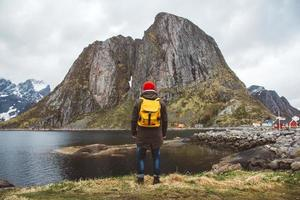 Traveler man with backpa standing on background of mountain and lake photo