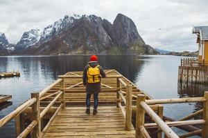 Traveler man standing on background of mountain and lake wooden pier photo