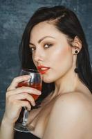 Beautiful woman with glass of wine on gray background photo