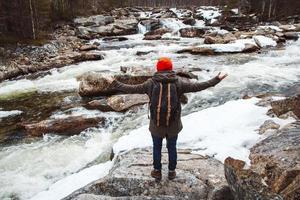 Hombre viajero de pie sobre una roca en el río y la cascada de la montaña foto