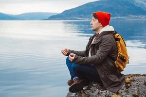 Traveler man in a meditative position sitting on a rocky shore photo