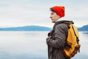 Portrait of a traveler standing on background of mountain and lake photo