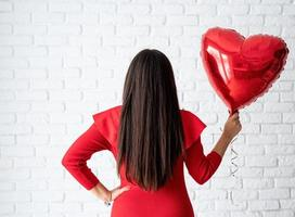 Young brunette woman in red dress holding a red heart balloon photo