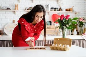 Woman in red dress making valentine cookies at the kitchen photo