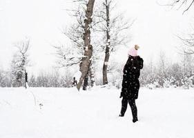 Vista trasera de la mujer morena caminando en el parque cubierto de nieve en la nieve foto