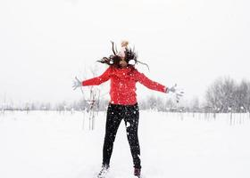 Young brunette carefree woman in red sweater jumping in snow outdoors photo
