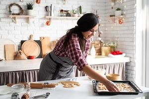 Young brunette woman baking cookies at the kitchen photo