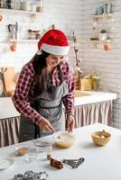 Young latin woman mixing dough cooking at the kitchen photo
