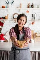 Happy brunette woman holding heart shaped dough at the kitchen photo