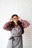 Happy woman in apron holding star shaped cookies in front of her eyes photo