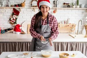 Young latin woman pouring flour to the dough cooking at the kitchen photo
