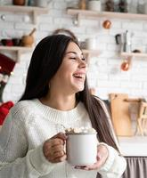 Brunette woman holding a cup of marshmallow cocoa in the kitchen photo