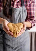 Woman hands holding heart shaped dough photo