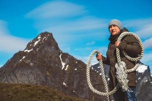 Man with a rope on his shoulder against a background of mountains photo