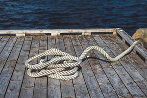 Cuerda de amarre en el muelle de madera foto