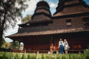 Married couple outside a wooden house photo