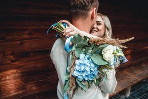 Married couple embracing with bouquet photo