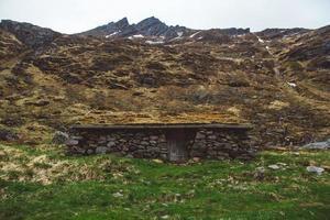 Antigua casa de piedra y madera cubierta de musgo. foto