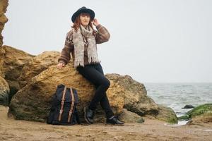 mujer en un sombrero con una mochila en el fondo del mar y las rocas foto