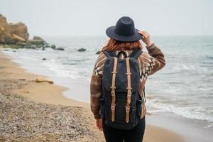 Woman in a hat with a backpack on background of sea and rocks photo