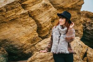Mujer con sombrero y bufanda sobre fondo de rocas foto