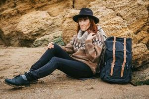 Woman in a hat and a scarf with a backpack sitting on the beach photo