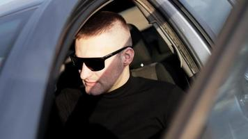 Side view of confident young stylish man in sunglasses in his car photo