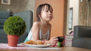 linda chica asiática en ropa casual está jugando videojuegos. video
