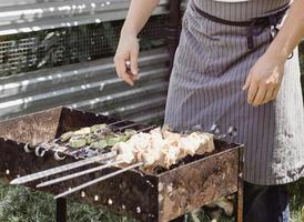 Young man grilling kebabs on skewers, man grilling meat outdoors photo
