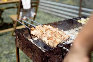 Close up of kebabs on skewers, man grilling meat outdoors photo