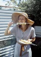 Mujer joven con sombrero de verano oliendo verduras asadas al aire libre foto
