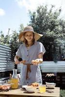 Mujer joven con sombrero de verano asar carne al aire libre en el patio trasero foto