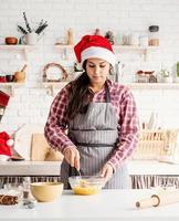 Young latin woman whisking eggs cooking at the kitchen photo