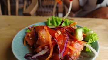 Mano de primer plano de cámara lenta con palillos para comer ensalada de salmón en la mesa video