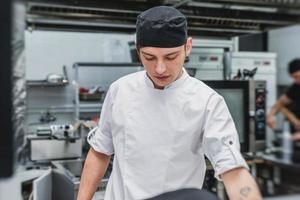 Young cook in white uniform working at the kitchen of the restaurant photo