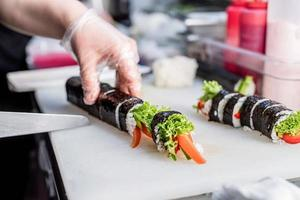 Sushi chef slicing rolls photo