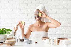 Mujer joven vistiendo toallas blancas aplicando mascarilla facial spa foto