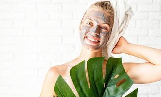 Feliz mujer sonriente en su rostro sosteniendo una hoja de monstera verde foto