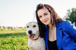 Hermosa joven sentada en la hierba abrazando a su perro en el parque foto