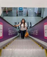 Young woman standing on escalator in shopping mall shopping photo