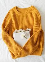 Top view of a book with white chrysanthemum flowers on yellow sweater photo