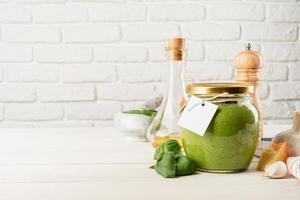 Salsa de pesto casera en un frasco de vidrio con una etiqueta en blanco, diseño de maqueta foto