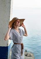 Happy woman in summer clothes standing by the sea looking away photo